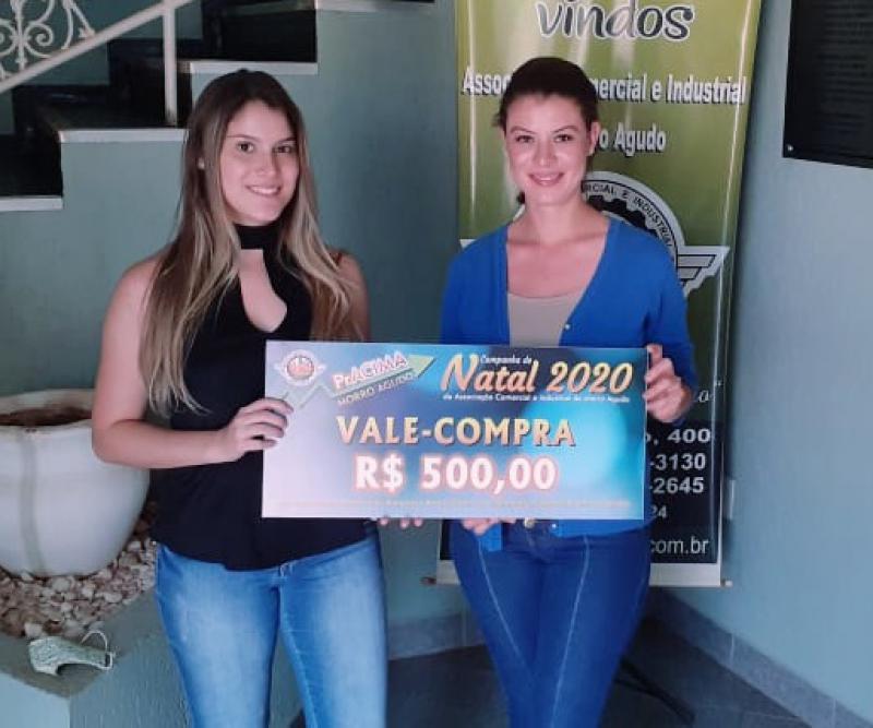 Foto: Marina Voltarelli (Secretaria da ACIMA) entregando vale-compras para Ana Carolina de Castro que comprou no E.R Cabeleireiro.