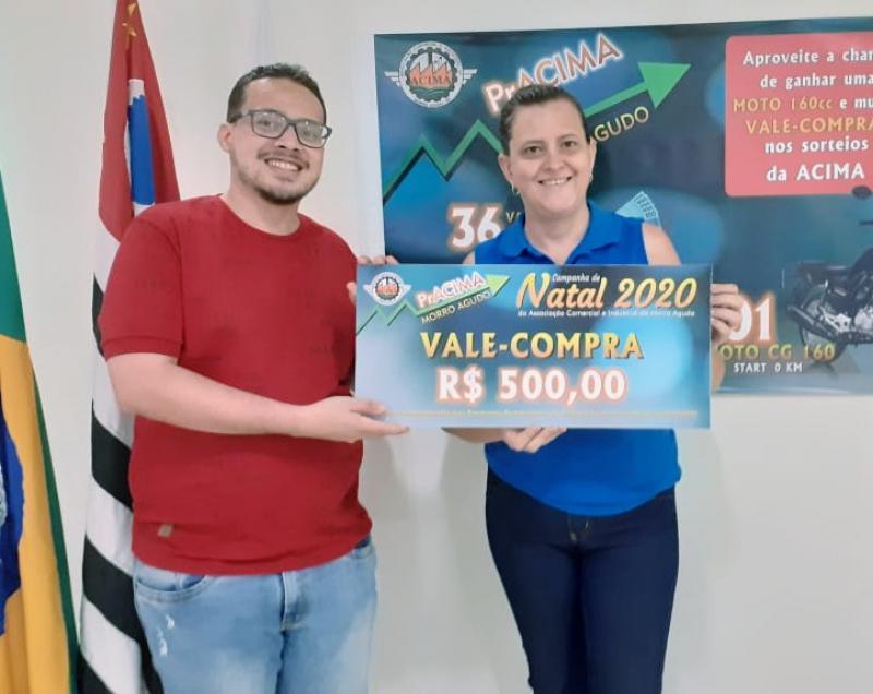 Foto: Neto Guimarães (Auxiliar Executivo da ACIMA) entregando vale-compras para Edma Cristina Alves Medeiros que comprou no Supermercado Chaim.