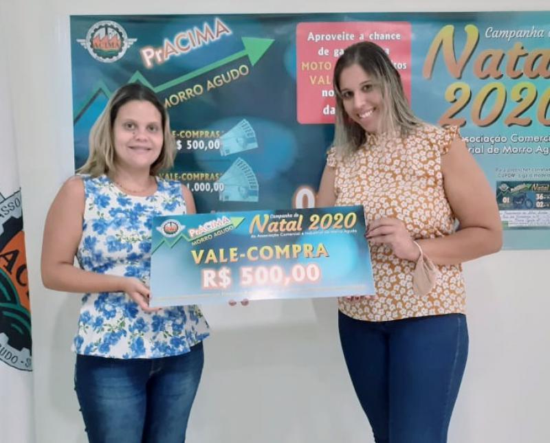 Foto: Ingridy Silva (Estagiaria da ACIMA) entregando vale-compras para Juliana Marques de Sousa que compra na loja Cara de Anjo.