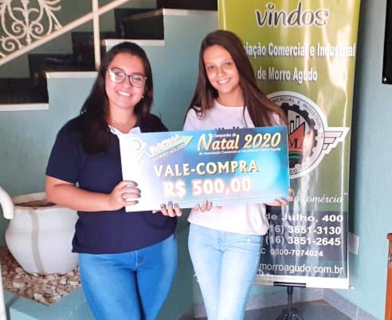 Foto: Sabrina Santos (Funcionária da Papelaria Copiart) entregando vale-compras para cliente Carolina Ehremberger.