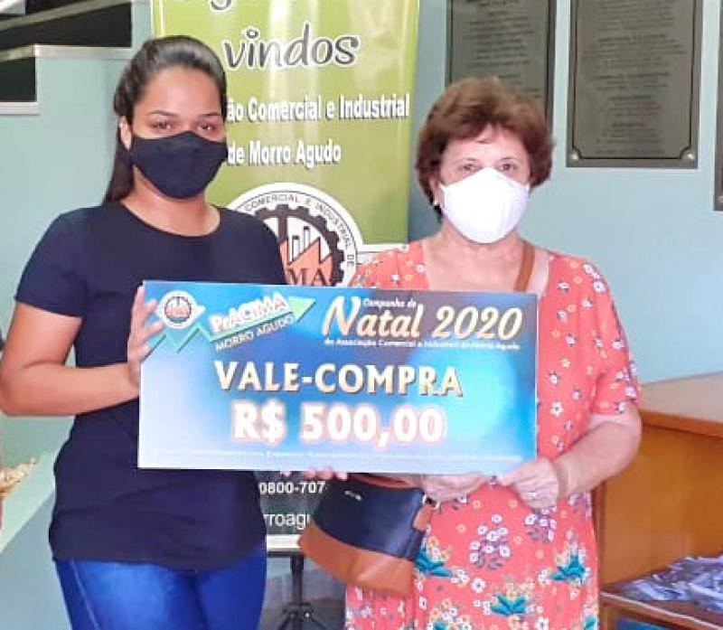Foto: Sabrina Martins (Funcionária da Stilly Calçados) entregando vale-compras para cliente Maria Aparecida Montovani Moraes.