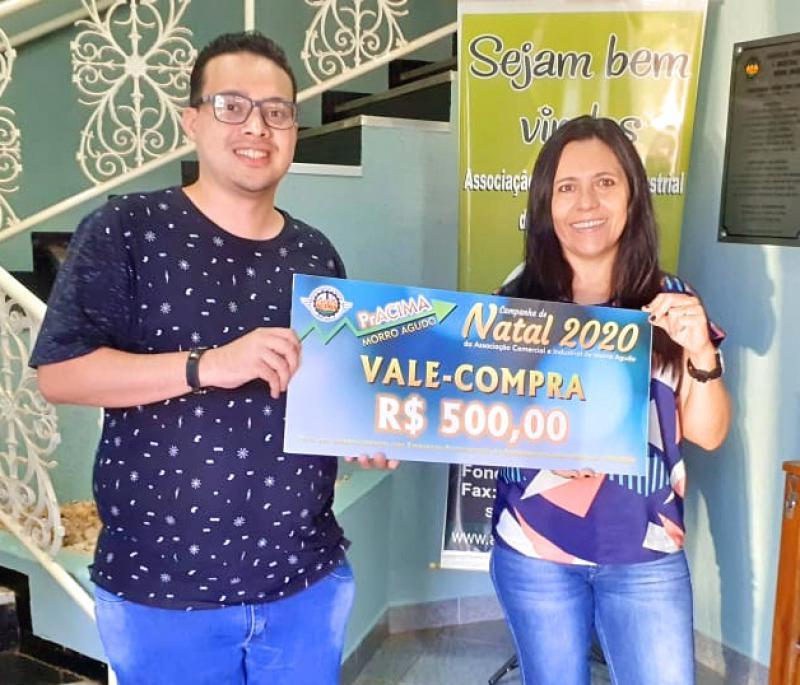 Foto: Neto Guimarães (Funcionário da ACIMA) entregando vale-compras para Giseli Fabiani de Souza que comprou na Mercearia do Natal.