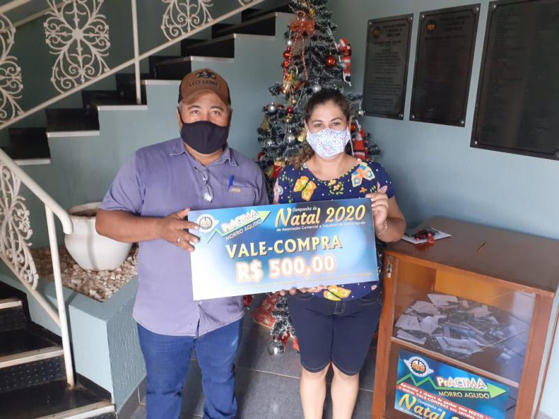 Foto: Clóvis Thomaz Theodoro (funcionário do Posto Safra) entregando o prêmio para Janaina dos Santos.