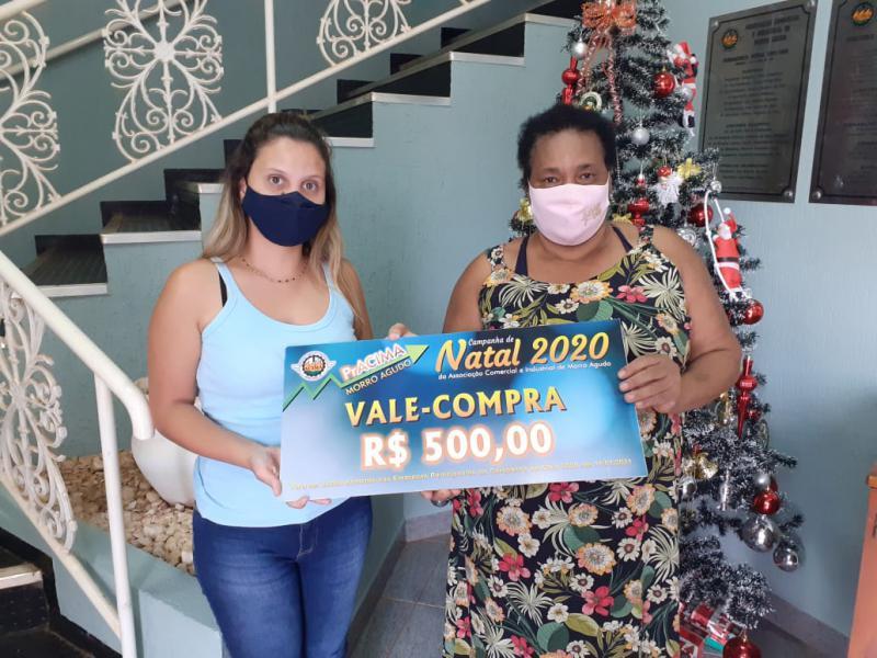Foto: Ingridy Silva (Estagiaria da ACIMA) entregando prêmio para Lourdes Aparecida da Silva cliente da Mercearia do Natal.