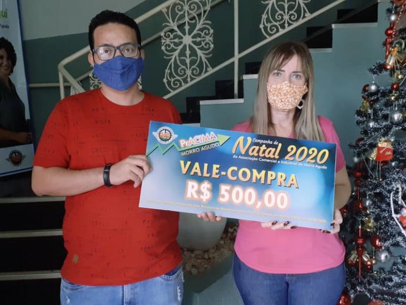 Foto: Neto Guimarães (Auxiliar Executivo da ACIMA) entregando prêmio para Aline Marcorio cliente do Supermercado Chaim.