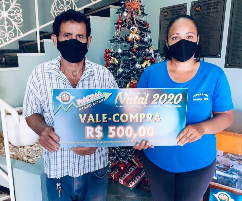 Foto: Tais Cristina (Funcionária da Funerária Santa Rita) entregando prêmio para cliente Valentin Aparecido Coelho.
