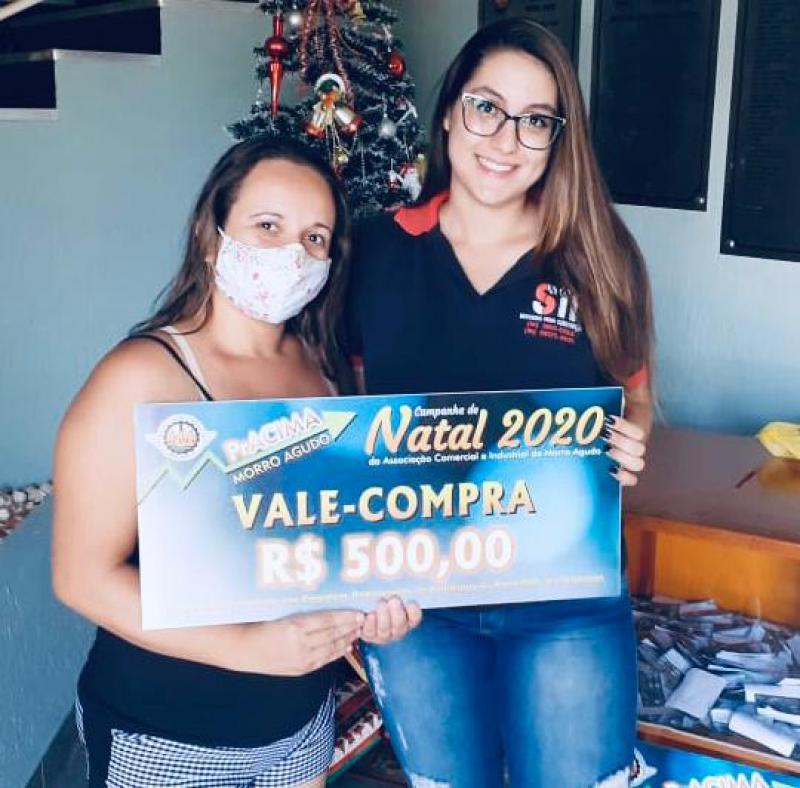 Foto: Inês Rissato (Funcionária da Sil Elétrica) entregando prêmio para cliente Maila Aparecida Dionísio.