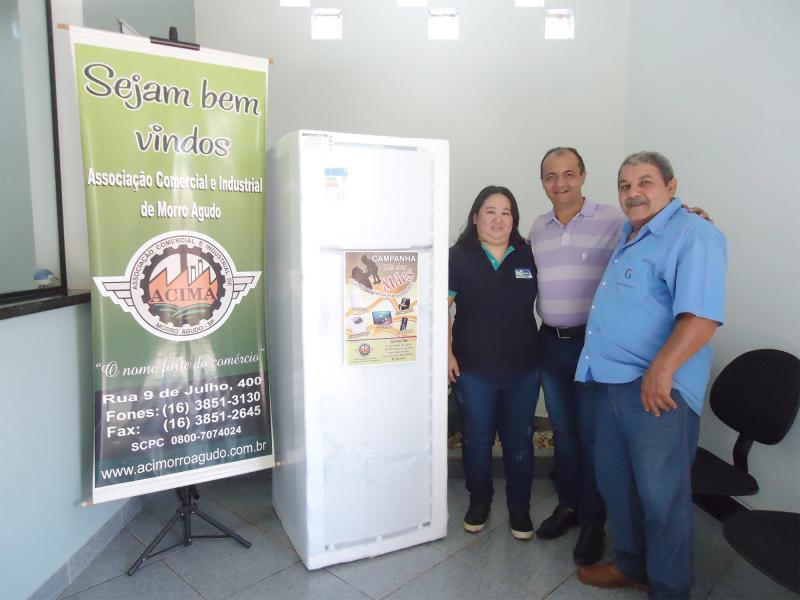 1º Prêmio: Uma Geladeira Duplex - Ganhador: Pedro Francelino - Empresa que comprou: Massa's Restaurante - Foto: Luciana (Proprietária da empresa) e Rogério Chiaroti (Presidente da ACIMA) com o ganhador.